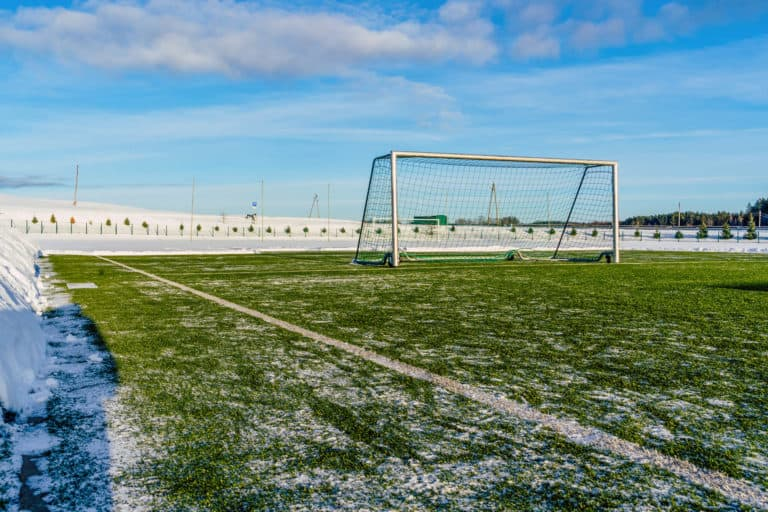Empty Soccer Field in the Winter Partly Covered in Snow - Sunny Winter Day, Concept of Winter Sports and Game (1)