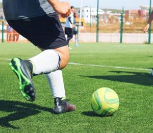 Soccer player kicking the ball on artificial turf (is soccer a winter or fall sport?)