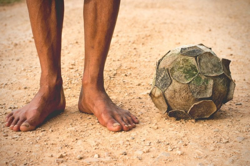 old soccer ball The legs of a man standing with a soccer ball on a dirt old, vintage tone.
