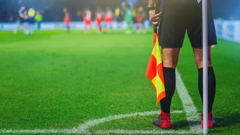 lineman assistant referee at the corner of a soccer field e1571233452193