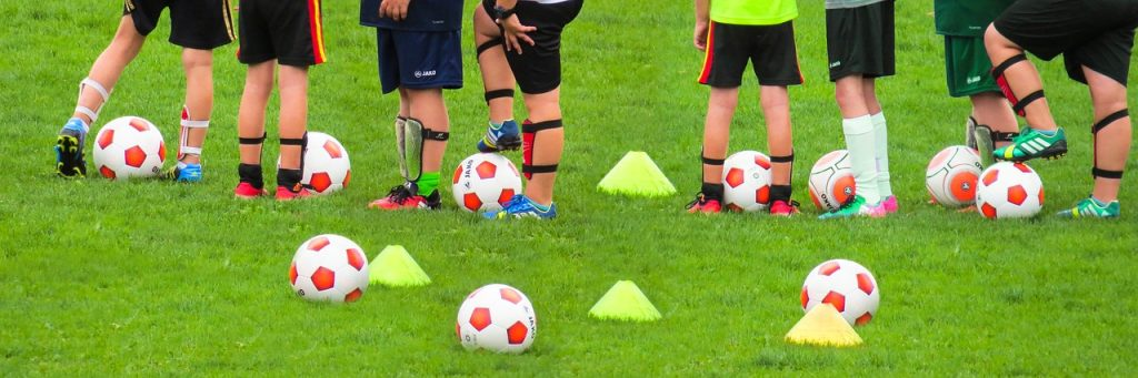 Soccer players stood on a training field with balls and cones on the ground.