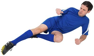 soccer player on the ground in a slide tackle