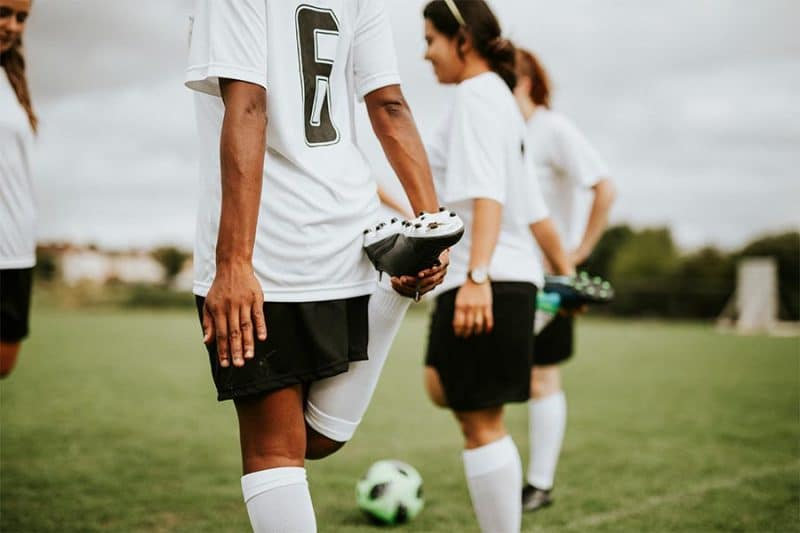 soccer players stretching before a game with feet behind their backs (playing soccer FAQ)