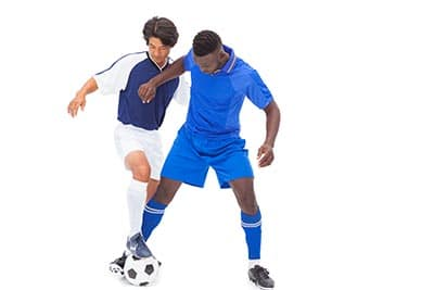 tackling and holding off two soccer players