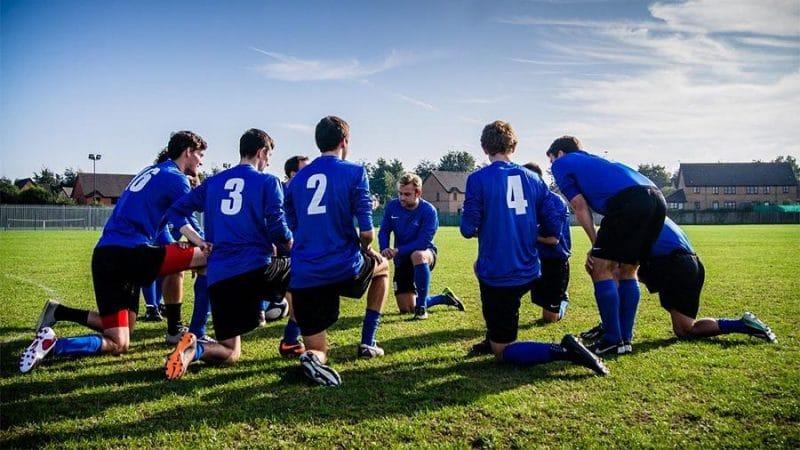 Soccer team on their knees on a field e1578134437353