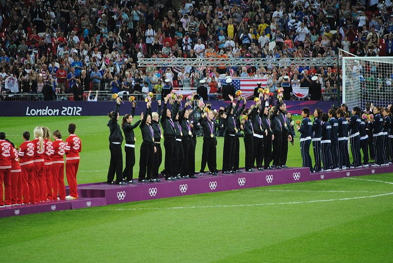 Soccer at the Olympics US Womens lifting trophy and medals - (what is soccer?)