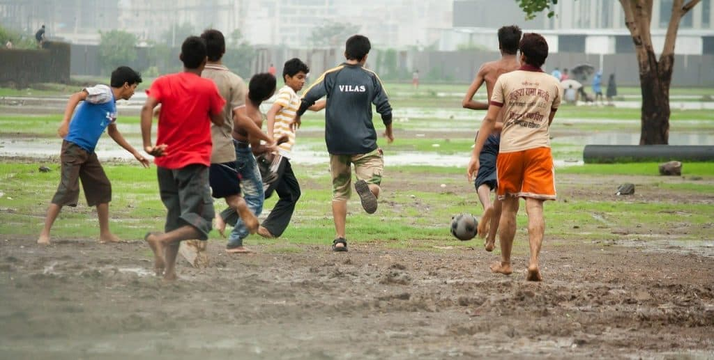 Kids playing soccer on rain soaked mud (are soccer games canceled for rain?)