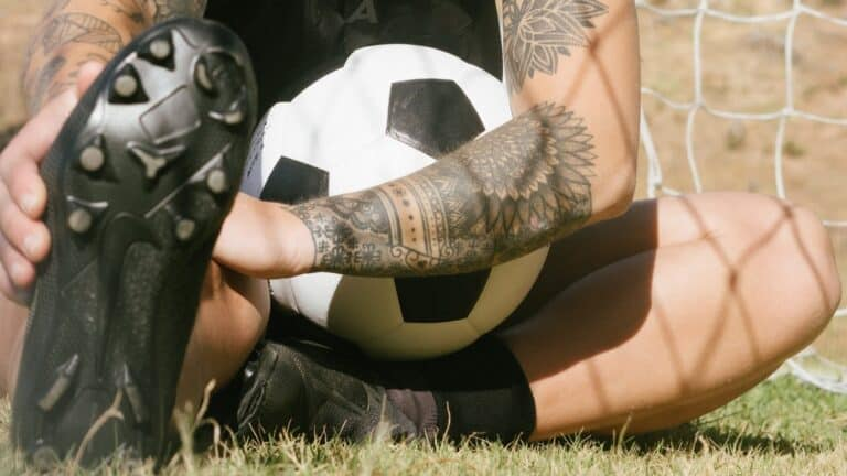 ○ Best Soccer Cleats For Players With Wide Feet: Top 3 ○ Soccer player touching wide flat cleats scaled e1603194912465