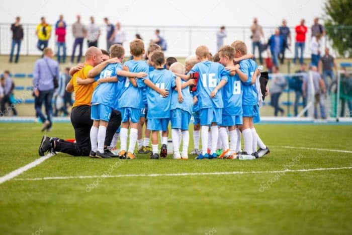 Youth Soccer Team in a Huddle with their Coach