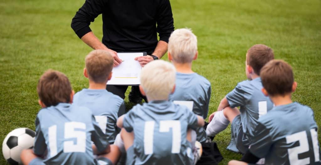 Coach Encouraging Boys Soccer Team. Soccer Football Team with Coach at the Stadium. (1)