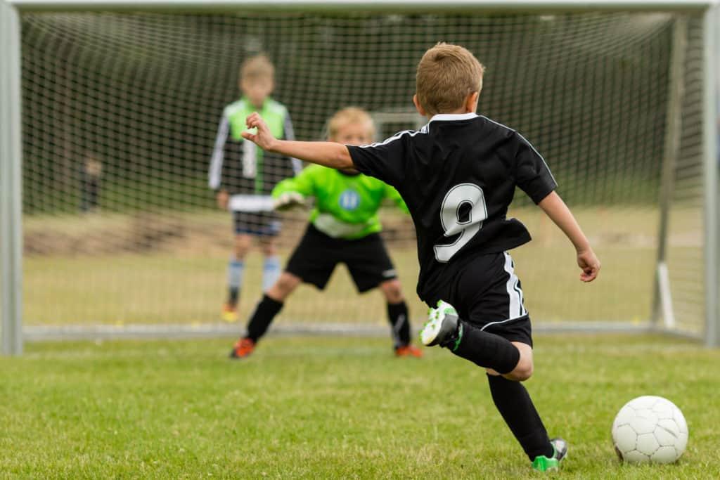 Soccer Player Kid Shooting At Goal