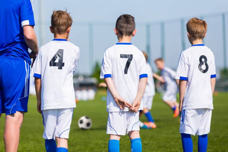 Youth Soccer Players With Their Soccer Coach Watching A Game