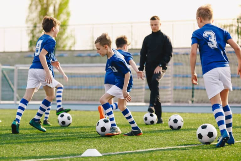 Group of school children playing training game with young coach. Kids playing and kicking soccer balls on grass pitch