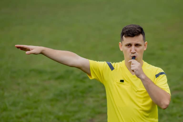Soccer Referee Signals For A Foul - Pointing towards the opposition goal for the attacker kick.