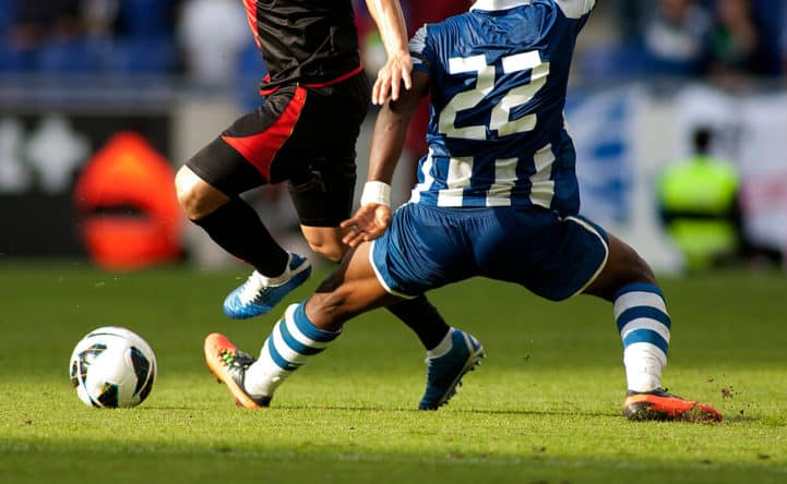 Two Soccer Players Challenging For The Ball