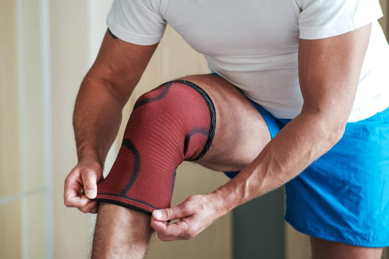 A man puts a sports knee pad on an injured knee before training