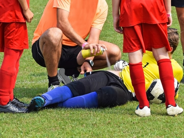 Injury in Soccer a player on the ground with physio