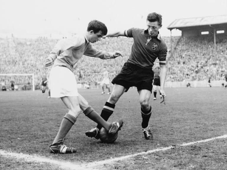 An Old Soccer Game in Black and White A player wearing glasses