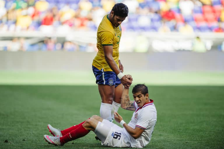 Brazil's Hulk helping a player off the ground