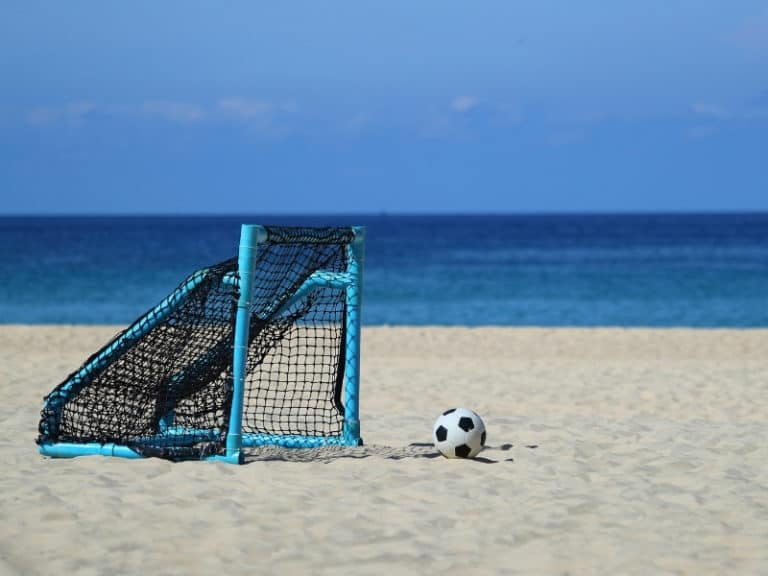 Soccer ball and goal on a beach